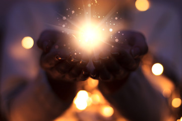 Magic particles emanating from female hands. Christmas background with bokeh