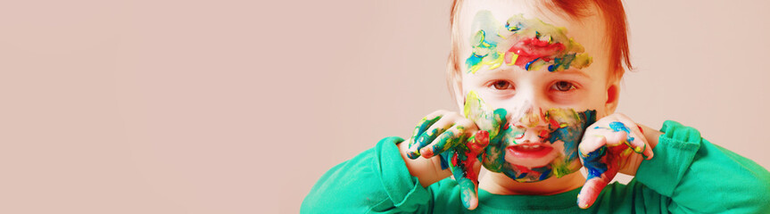 Art, creative and happiness childhood concept. Colorful painted hands and face in a beautiful young girl.