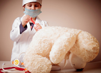Little cute child girl playing doctor and makes injection of teddy bear. Health, medicine, hospital concept.