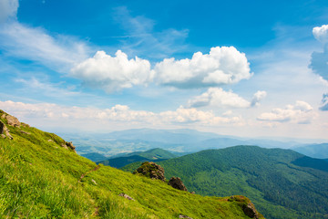 rock on grassy slope of a mountain. beautiful view from the top of a hill. wonderful summer landscape on a sunny day. beautiful clouds on a blue sky