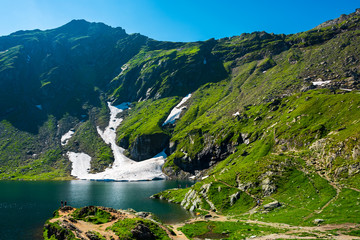 Lake Balea of Fagaras mountains. last pieces of snow on the grassy hills. beauty of Romania