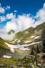 wonderful springtime scenery in mountains. rocky slope with green grass and spots of snow. clouds rising around the distant peak. beautiful sunny weather