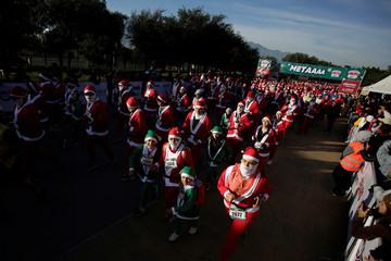 "Participants dressed as Santa Claus take part in the annual race known as ""Run Santa Run"" at Fundidora Park in Monterrey"