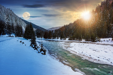 day and night time change concept. mountain river in winter with sun and moon. snow covered river banks. forest in snow on the distant mountain. cloudy morning