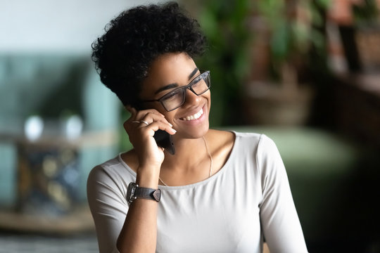 Happy African American woman talking on phone, having pleasant conversation with friend, holding cellphone, speaking, chatting by smartphone in cafe, smiling female receive good news, making call