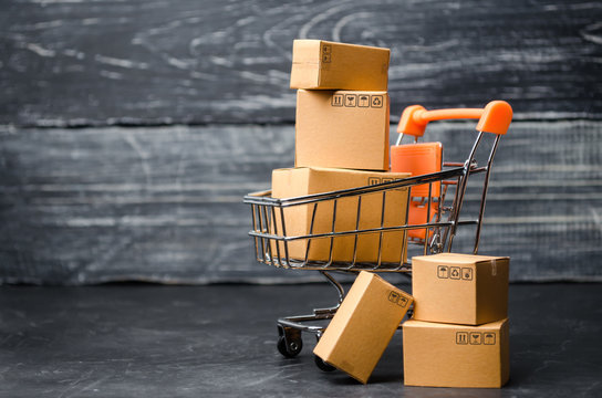 A supermarket cart loaded with cardboard boxes. Sales of goods. concept of trade and commerce, online shopping. high. delivery order. purchasing power of the population and the state of the economy