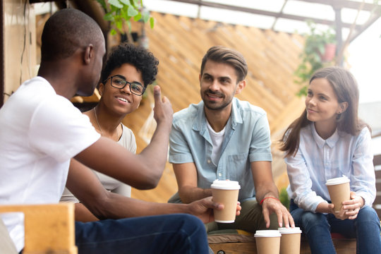 African American man showing thumb up, telling story to interested attentive friends, sitting, drinking coffee in cafe together, smiling multiethnic friends discussing, talking, chatting