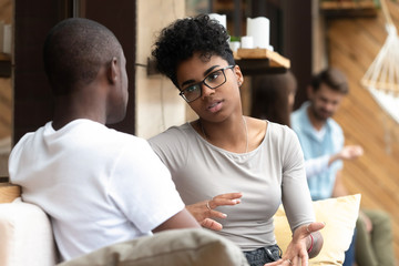 Focused African American woman talking with man in cafe, girlfriend discussing relationships with boyfriend, explaining, gesticulating, friends having serious conversation, sitting together on couch