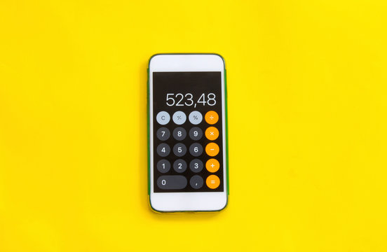 smart phone with calculator on yellow background