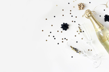 Happy New Year composition. Champagne wine bottle and glasses with golden confetti stars isolated on white table background. Party celebration concept. Flat lay, top view. Empty copy space.