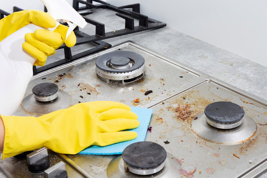 Cleaning a gas stove with kitchen utensils, household concepts, or hygiene and cleaning.
