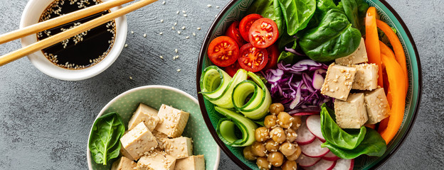 Buddha bowl salad with chickpeas, sweet pepper, tomato, cucumber, red cabbage kale, fresh radish, spinach leaves and tofu cheese, healthy balanced clean eating concept, top view, banner