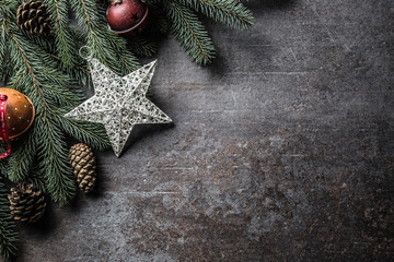 Top of view christmas star decorations jingle bells fir tree pine cones on free concrete background