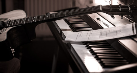 acoustic guitar stands on piano with notes, close-up, beautiful color background