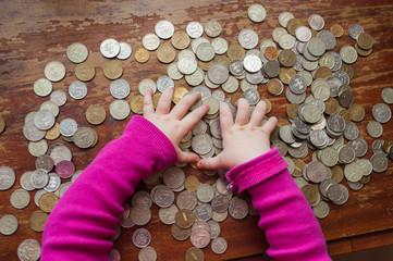 Children's hands lie on the Russian coins on a wooden table