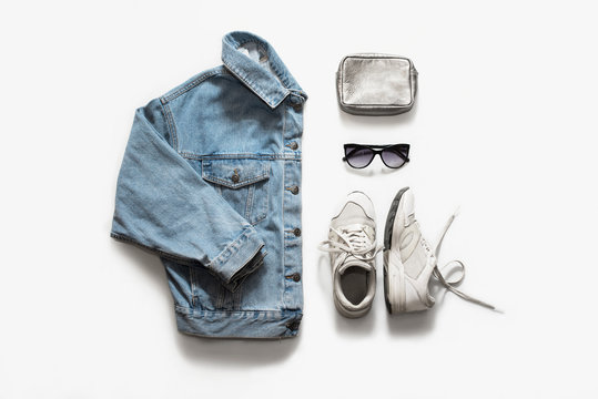 Casual fashion clothes and accessory set on white background. Jean jacket, sneakers, sunglasses, bag. Flat lay, top view.