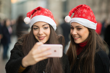 Smiling young women in Christmas hat taking a picture together
