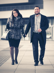 Happy young fashion couple in love walking on city street