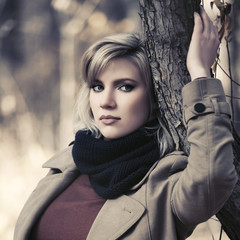 Sad young blonde fashion woman walking in autumn park