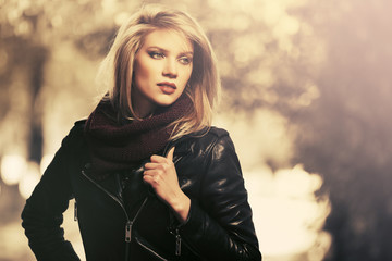 Young fashion blonde woman wearing leather jacket on city street