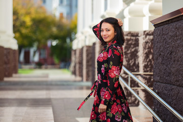 Happy young fashion woman in floral dress on city street