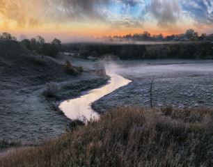 picturesque autumn dawn. beautiful clouds over the picturesque river. foggy morning