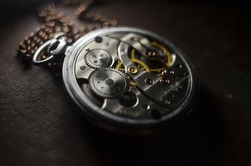 antique pocket watch on a vintage photo album. selective focus