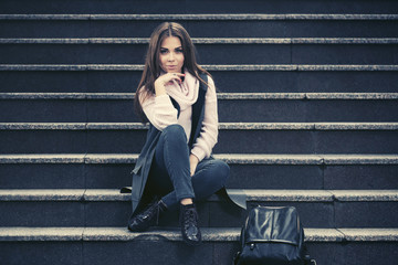 Happy young fashion woman in gray sleeveless coat sitting on steps