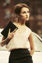 Young fashion business woman with handbag on city street
