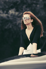 Young fashion woman in sunglasses leaning on her car