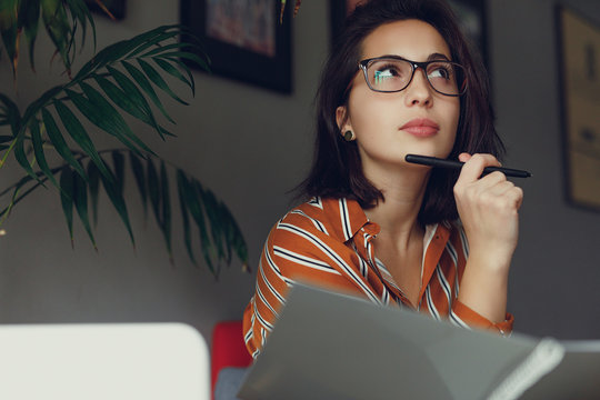 Businesswoman wear glasses in office, work on laptop and think about new ideas with pen. Girl using laptop for work, copy space