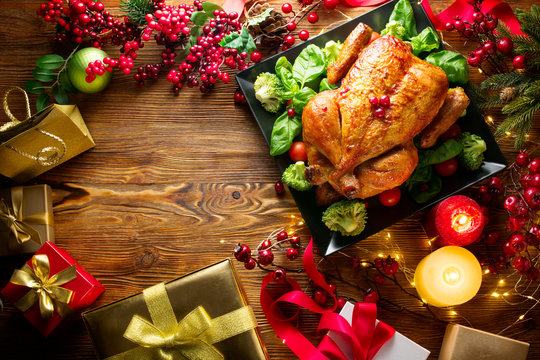 Christmas family dinner. Roasted chicken on holiday table, decorated with gift boxes, burning candles and garlands. Roasted turkey over wooden background. Top view, flatlay