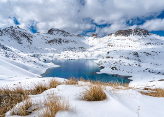 A very deep blue lake sits in a valley between snow capped mountains on a partly cloudy day