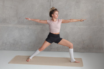 Young woman standing in Warrior pose