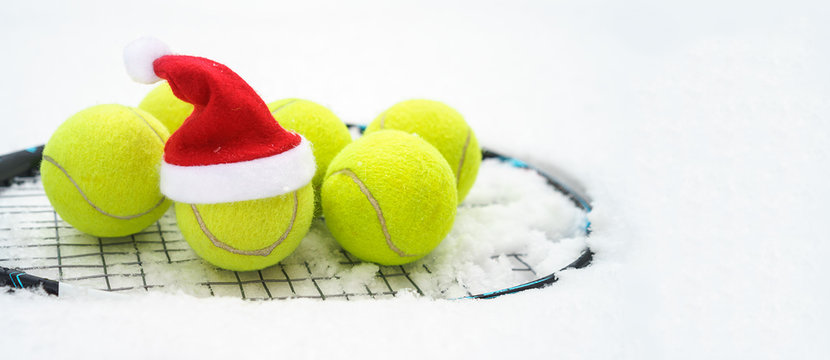 Santa hat on tennis ball, set of tennis balls on racket on white snow winter background. Merry Christmas and New year concept with tennis balls play. Close up, sport lifestyle, funny. Isolated