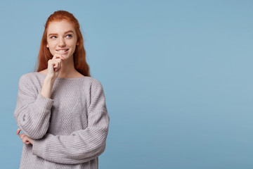 Red-haired beautiful girl stands holding her hand near the chin slightly bit her lip looking aside at the copy space, dreams, plots, plans, ponders ideas, cheerful playful mysterious look