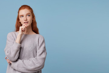 What if I call him, write, buy it? A red-haired mysterious young woman looks to the side on empty copy space holding her hand on her chin, her mouth slightly open