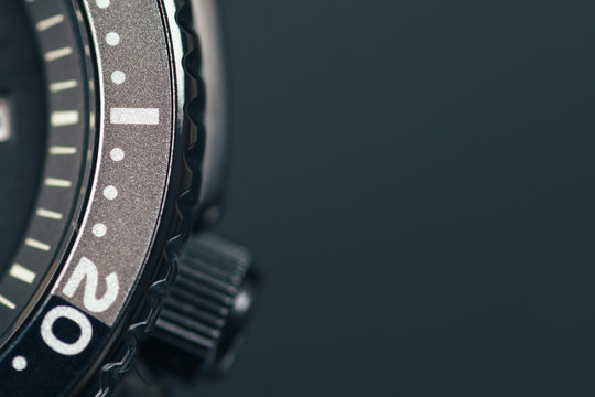 Watch close up dial, bezel and crown. Dark background. Copy space.