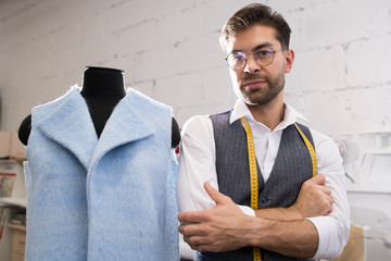 Waist up portrait of handsome male tailor posing standing next to mannequin in atelier studio