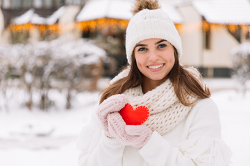 Portrait of a beautiful girl in white winter clothes on the street that holds heart to valentine day.