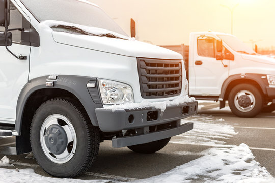 New middle size trucks at dealership parking outdoors at winter. Truck service and maintenance. Delivering and warehouse service