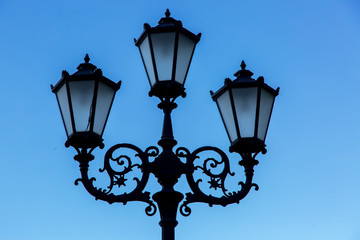 triple street lamp on the leg, a lantern in retro style black with forged patterns against the sky.