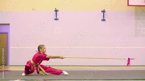 Young girl in red yifu clothes doing qiansho form exercises