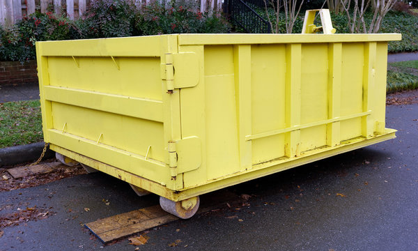 Freshly painted yellow industrial dumpster container deposited on neighborhood street. No lettering.