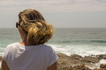 blond woman looking out to sea