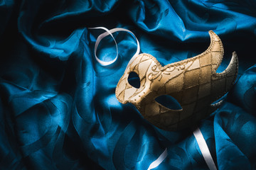 High contrast image of a venetian mask on blue fabric