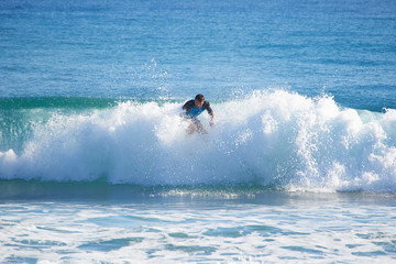 man in the ocean on a surfboard rides on top of a wave