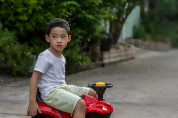 Black hair little asian child wear white shirt waiting to play, Alone 4 years old boy sitting on red toy ATV and looking for friends, image for kids sport or recreation concept