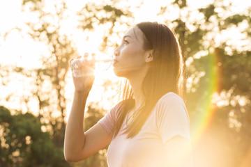 sport woman drinking water during morning jogging