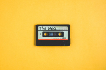 Old audio cassette tape on a yellow background